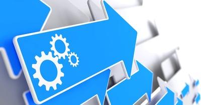 Cogwheel Gear Mechanism Icon on Blue Arrow on a Grey Background.
