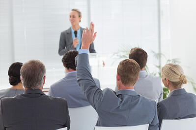 Pretty businesswoman talking in microphone during conference in meeting room