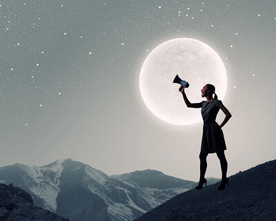 Young woman speaking in megaphone against full moon
